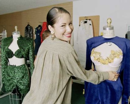 CORPUS CHRISTI, TX — Selena showing outfits she designed and planned to wear on stage in March 1995. Photo Credit: Houston Chronicle / Paul S. Howell.